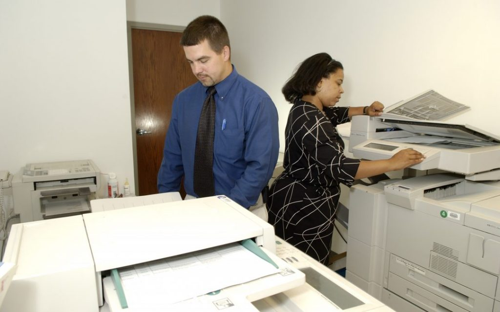 Man and women using printers in a designated photocopier room