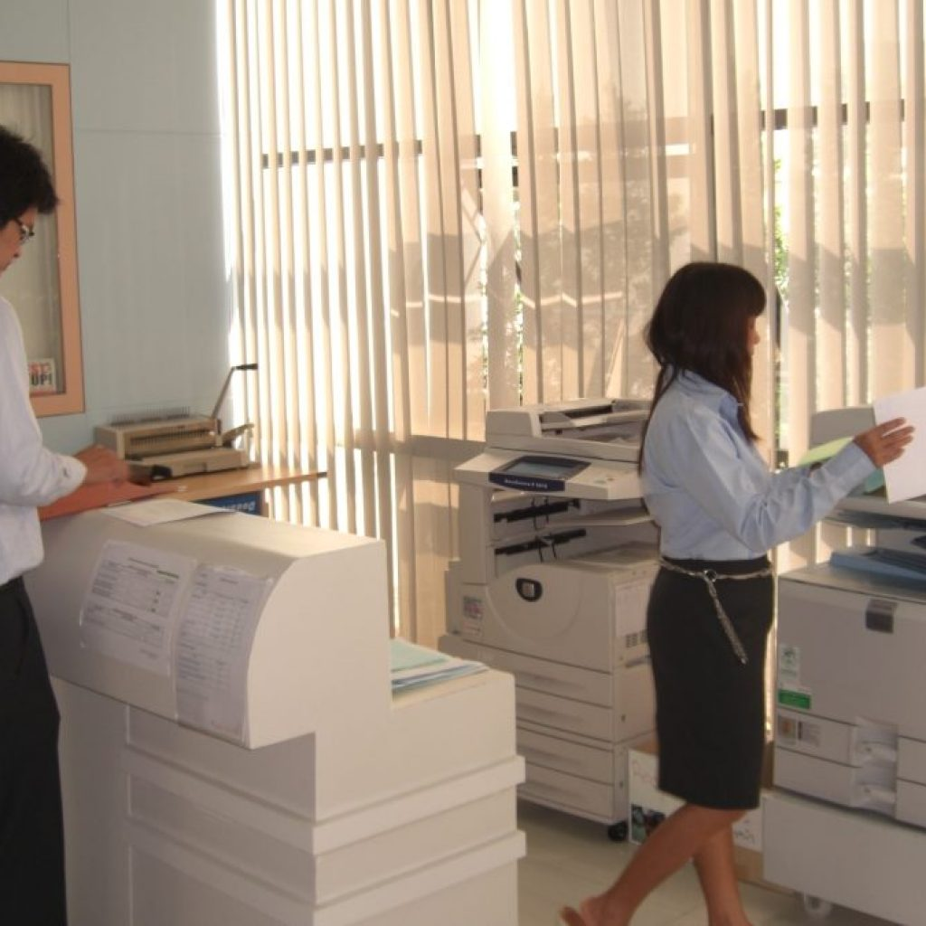 Man and woman sorting documents in a photocopier room