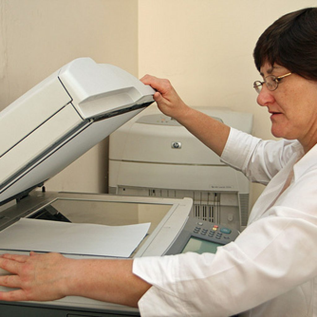 Women using the scanner function on an office computer