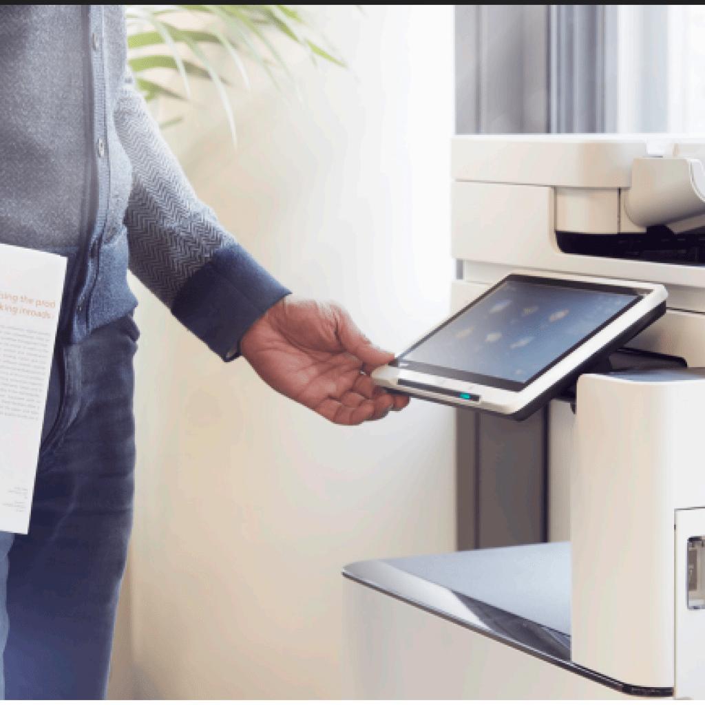 man in an office using a touchscreen printer