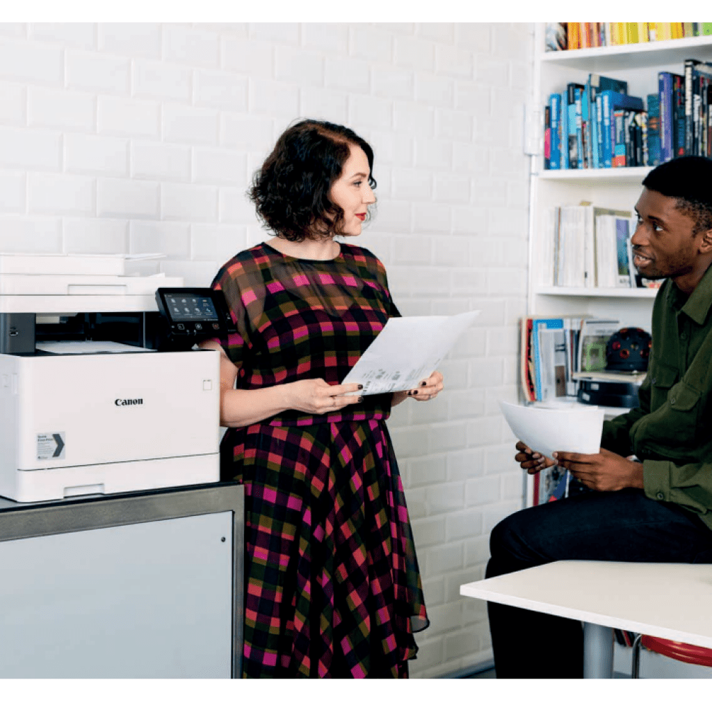 Two people talking at a printer